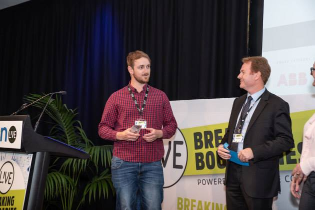 Paul Burrows, HVAC Segment Manager for ABB in Australia on stage presenting the Male Rising Star award to Mitchell Beattie, Service Technician of Engie Services