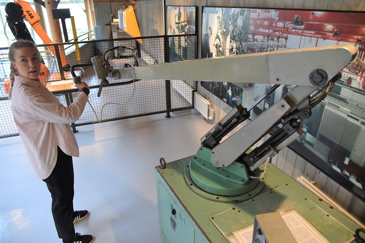 Videoreporter Marte Lie i ABB demonstrerer programmering av verdens første lakkeringsrobot fra 1969, nå pensjonert på museet Vitengarden på Jæren