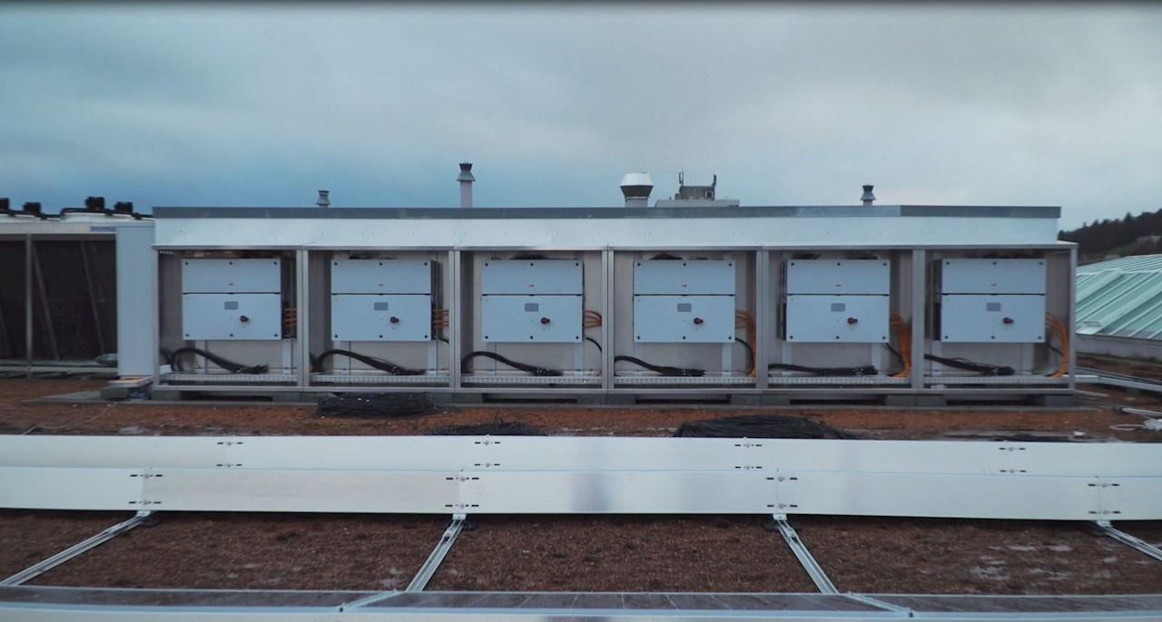 Dreiphasiger String-Wechselrichter PVS-100 auf dem Dach eines Coop-Supermarktes.