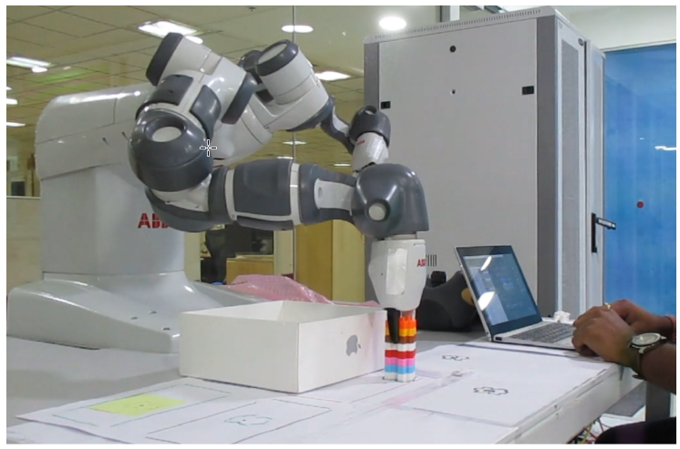 Figure 3: The robotics lab set up for Task #1. The LEGO-like object is being picked in order to be placed in the white box.