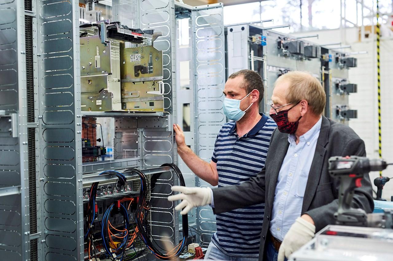 Jonatorin myyntipäällikkö Arttu Uotila esittelee työn alla olevaa kojeiston valokaarisuojauksen keskusyksikköä Borealis Polymersin sähkökäytön johtajalle Jari Välilälle.